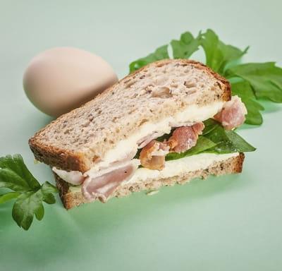 Бутерброд с беконом, яичным салатом и шпинатом