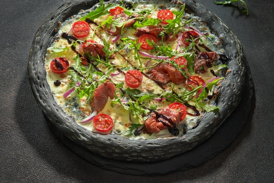 Чёрная пицца с ростбифом и рукколой